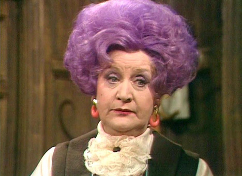 Mollie Sugden as Mrs Slocombe